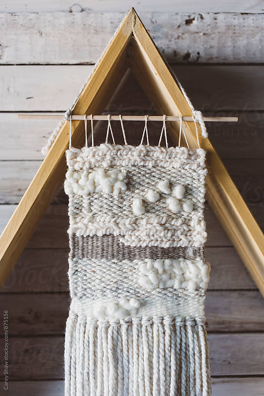 Wall weaving hanging on triangle shelf by Carey Shaw for Stocksy United