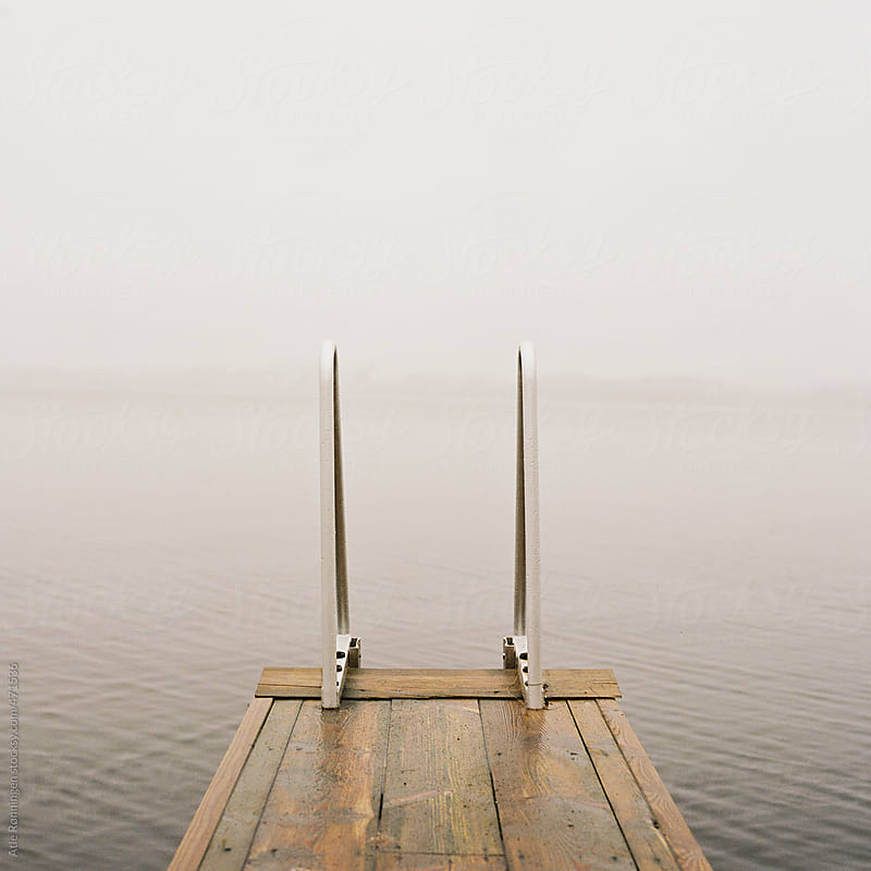 Bathing ladder on a small jetty with foggy horizon by Atle Rønningen for Stocksy United