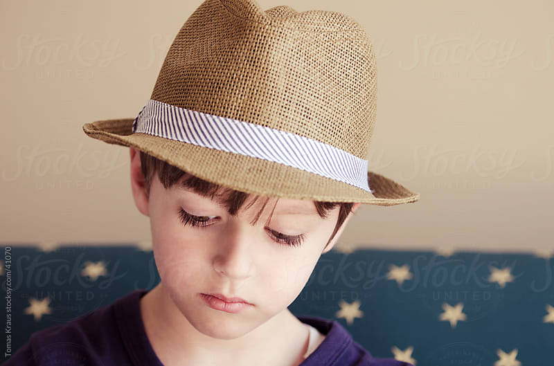 expressions of a boy in a hat by Tomas Kraus for Stocksy United