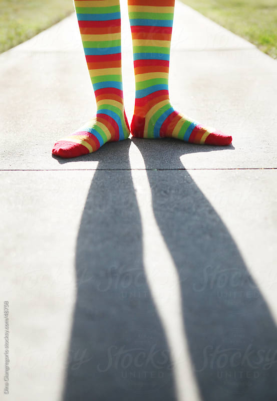 Lower leg crop of child wearing striped colorful socks standing on sidewalk with long shadow showing by Dina Giangregorio for Stocksy United