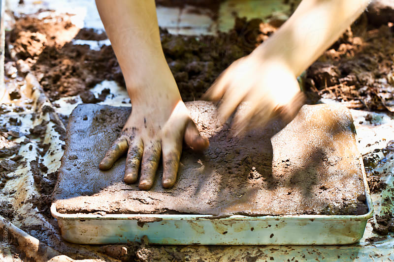Child Playing in Mud by Jill Chen for Stocksy United