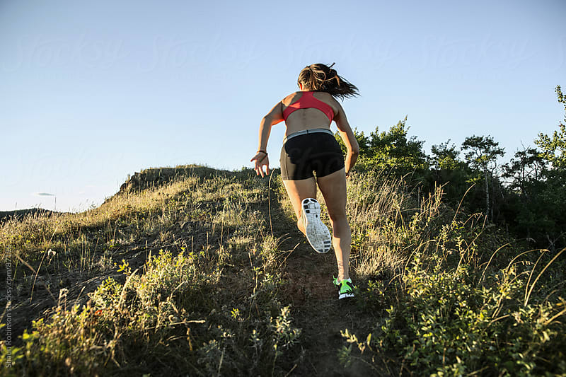 a young fit woman running up a hill by Shaun Robinson for Stocksy United