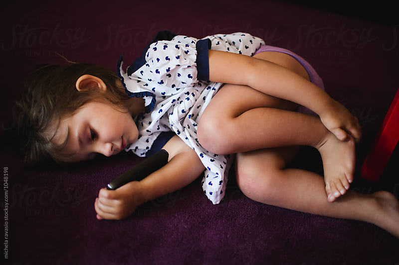 Little girl lying on the carpet watching the cartoons on the cell by michela ravasio for Stocksy United