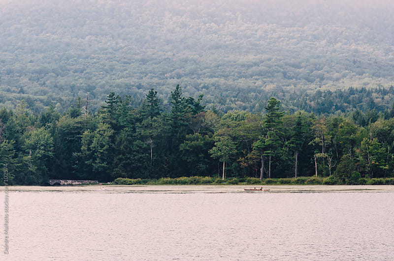 Lake in the Catskill Mountains with kayakers in distance by Deirdre Malfatto for Stocksy United
