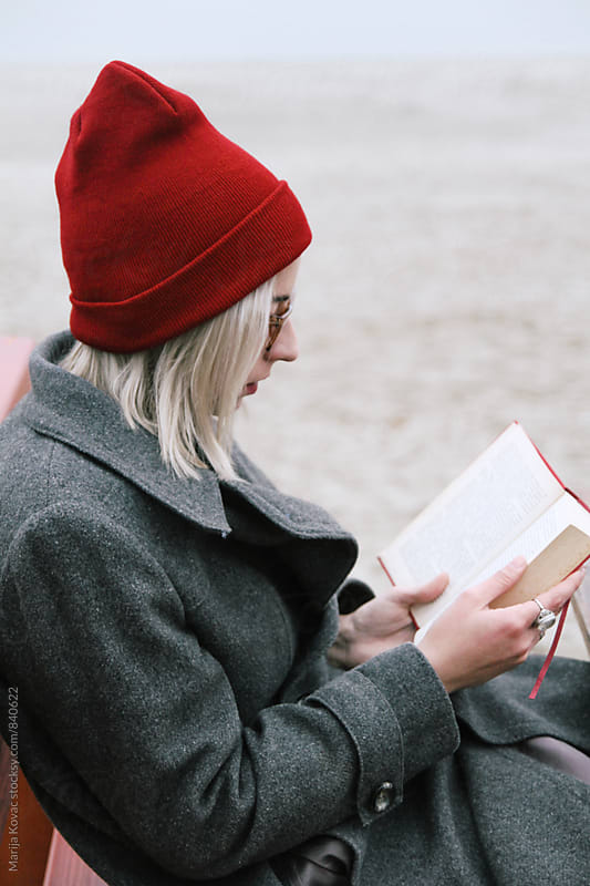 Young woman reading a book outdoor, vertical by Marija Kovac for Stocksy United