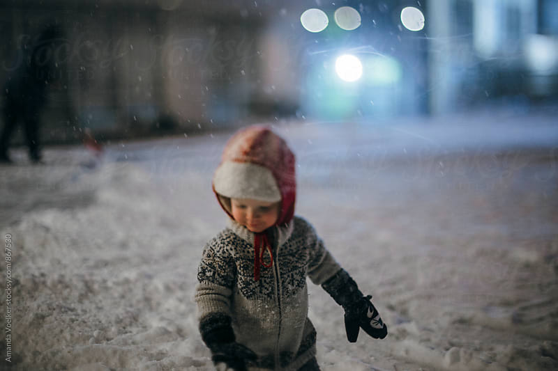 A Toddler Boy Plays Outside in the snow by Amanda Voelker for Stocksy United
