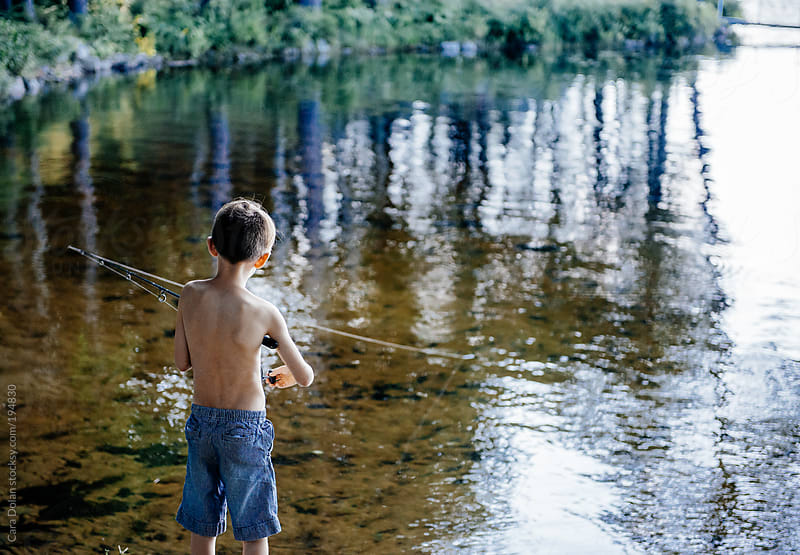 Boy goes fishing at the edge of a lake in summer by Cara Dolan for Stocksy United