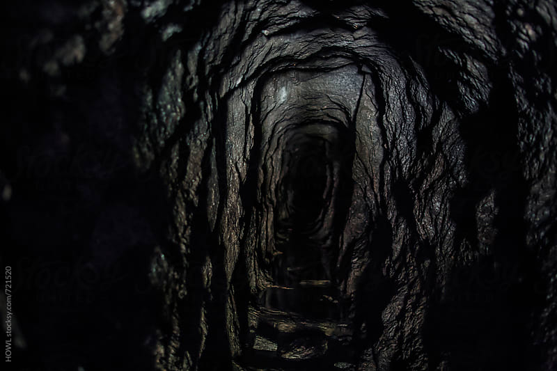 A dark and intimidating cave leading into a ominous hole  by HOWL for Stocksy United