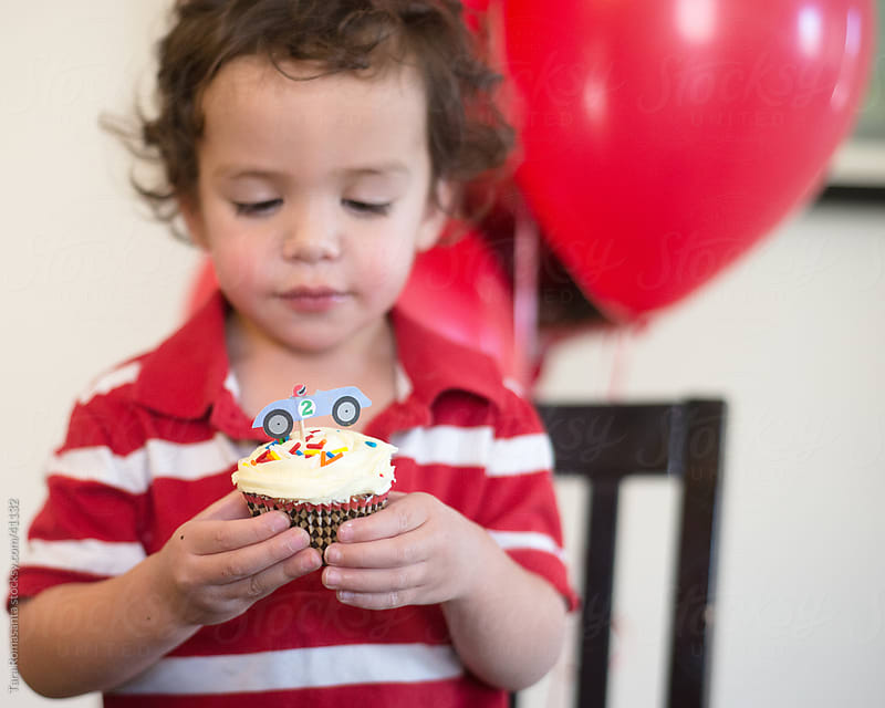 boy eyes a cupcake on his second birthday by Tara Romasanta for Stocksy United