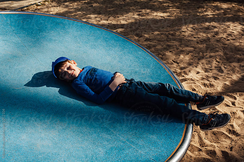 Boy taking a pretend nap on a playground by Mima Foto for Stocksy United