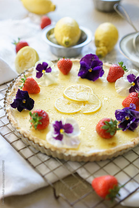 Tarte au citron garnished with fruit and flowers. by Darren Muir for Stocksy United