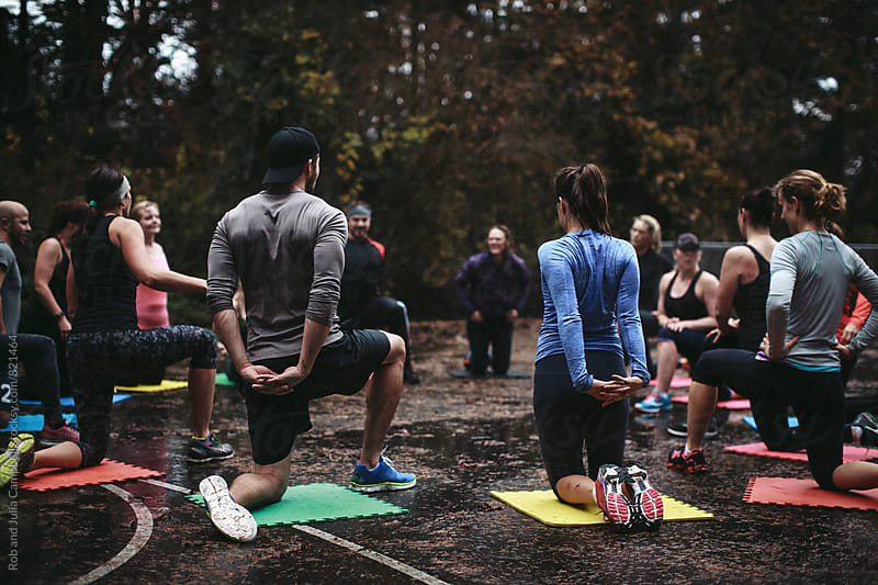 Fit people stretching arms and back outside in group workout by Rob and Julia Campbell for Stocksy United