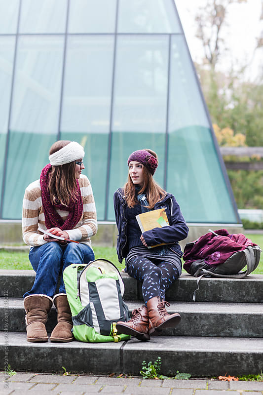 Two female college students sitting and talking on campus by Suprijono Suharjoto for Stocksy United