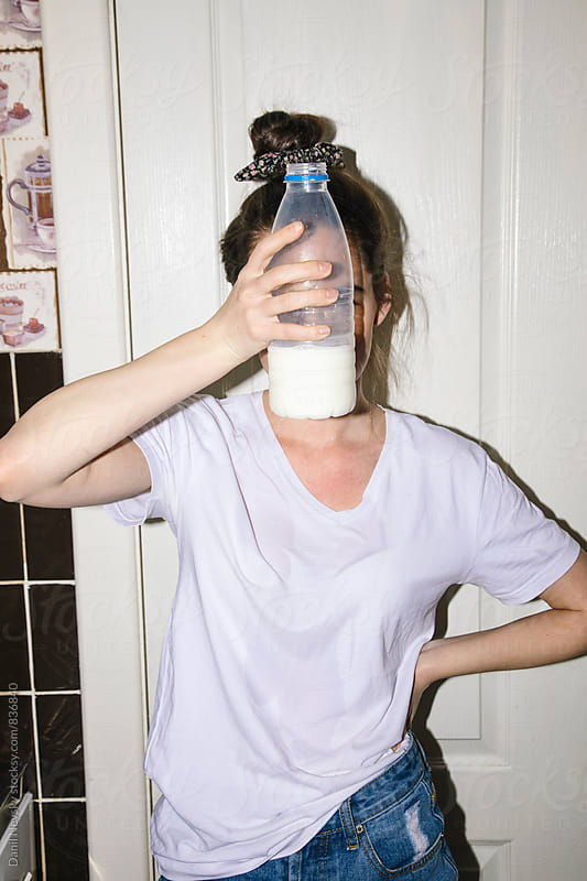 Young woman holding bottle of milk in front of her face by Danil Nevsky for Stocksy United