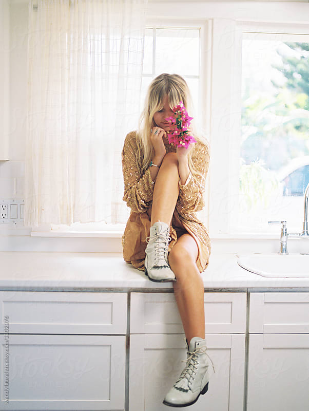 blonde girl with pink flowers and boots on kitchen counter by wendy laurel for Stocksy United