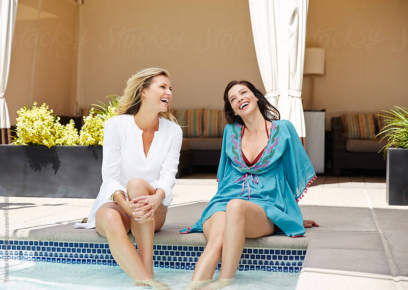 Girlfriends relaxing by the pool at luxury resort  by Trinette Reed for Stocksy United