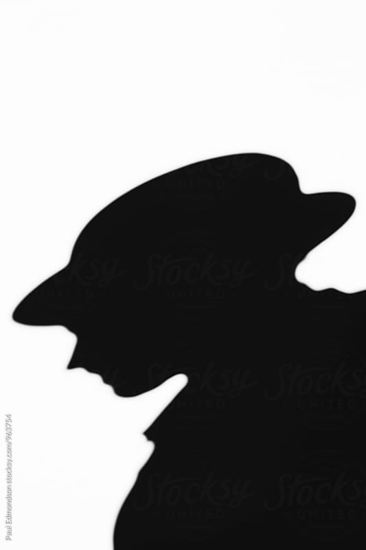 Shadow of man wearing fedora hat, blurred focus  by Paul Edmondson for Stocksy United