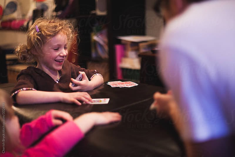 A family plays a game of cards. by Cherish Bryck for Stocksy United