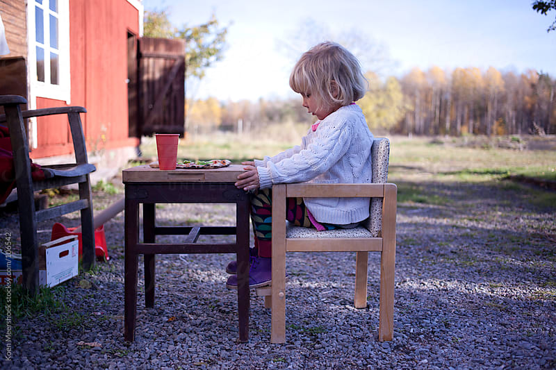 little girl having a small pizza for lunch outside. by Koen Meershoek for Stocksy United