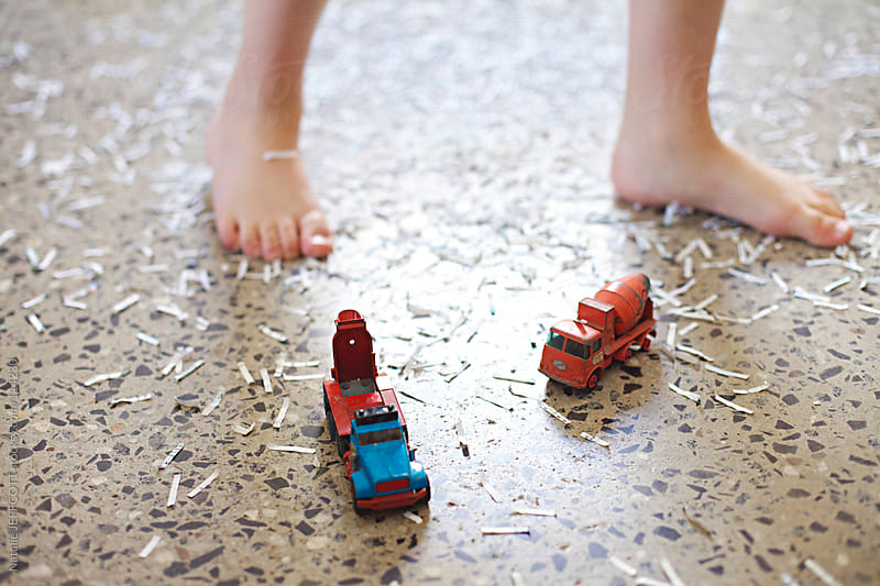 A young child's feet surrounded by shredded paper and pretending it's snow by Natalie JEFFCOTT for Stocksy United