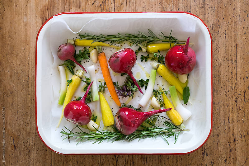 Roasting tray of fresh root vegetables and herbs by Rowena Naylor for Stocksy United