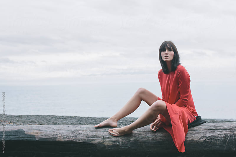 A woman sitting on a tree trunk at the beach by Ania Boniecka for Stocksy United
