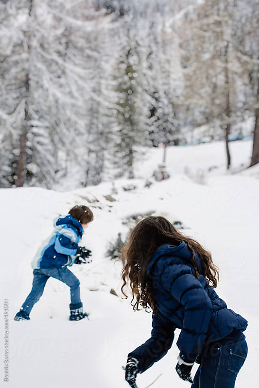 Siblings playing in the snow with joy by Beatrix Boros for Stocksy United
