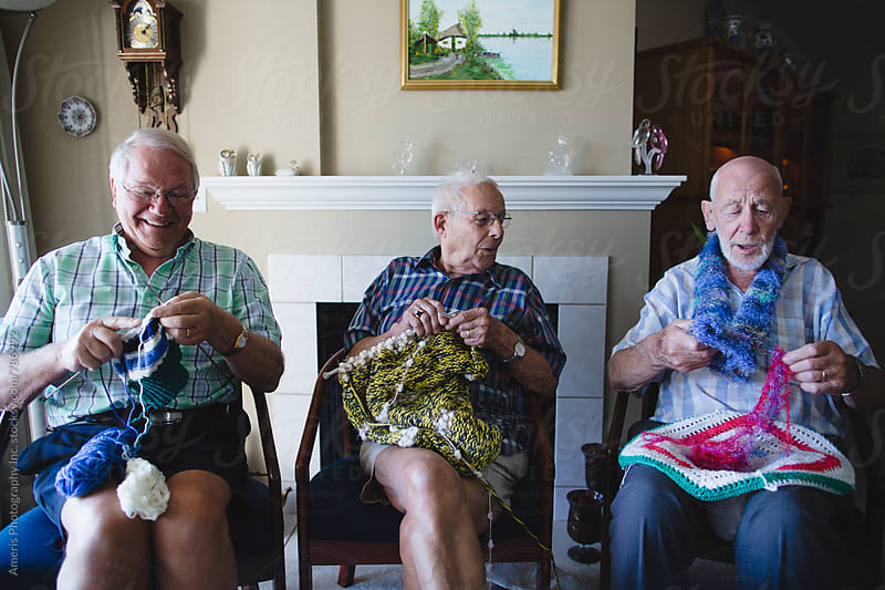 Group of senior men knitting together by Rob and Julia Campbell for Stocksy United