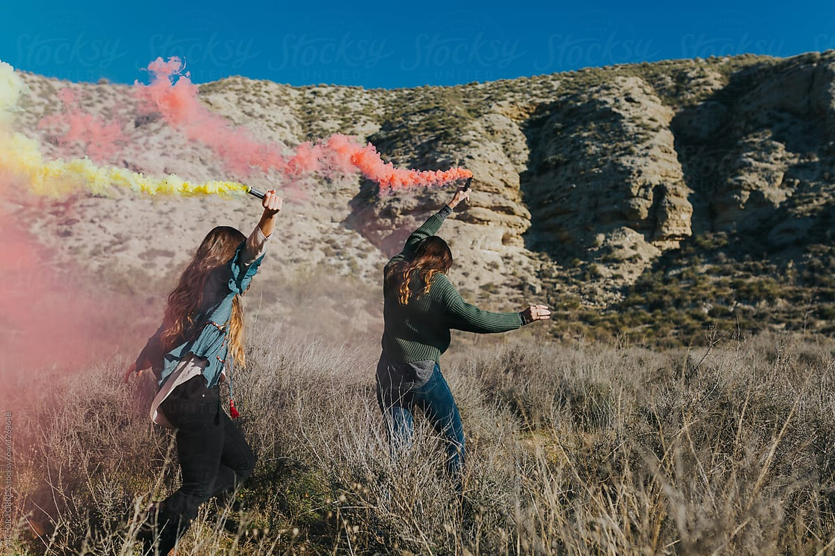 Stock Photo - Cheerful Teenagers Playing With Color Smoke Bombs In The  Country
