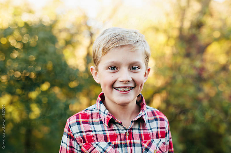 portrait of a happy boy in a flannel shirt by Kelly Knox for Stocksy United