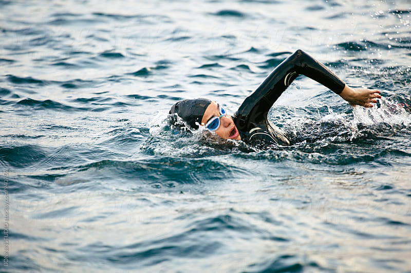 Woman wearing a wetsuit swimming in the sea. by BONNINSTUDIO for Stocksy United