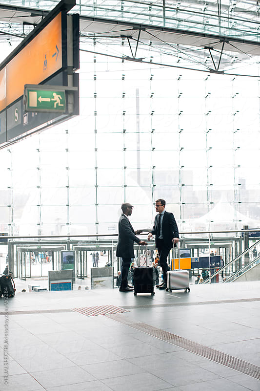 Two Young Business Travelers Chatting and Waiting in Bright Modern Glass Structure by Julien L. Balmer for Stocksy United