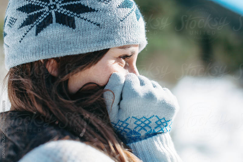 Closeup of a young woman on a cold snowy day. by BONNINSTUDIO for Stocksy United