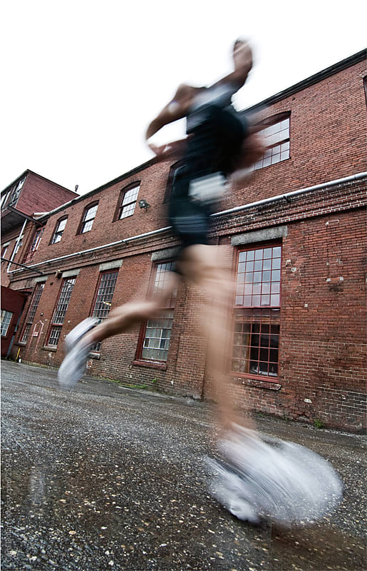 Runner in motion passes by old brick building during race by Cara Dolan for Stocksy United