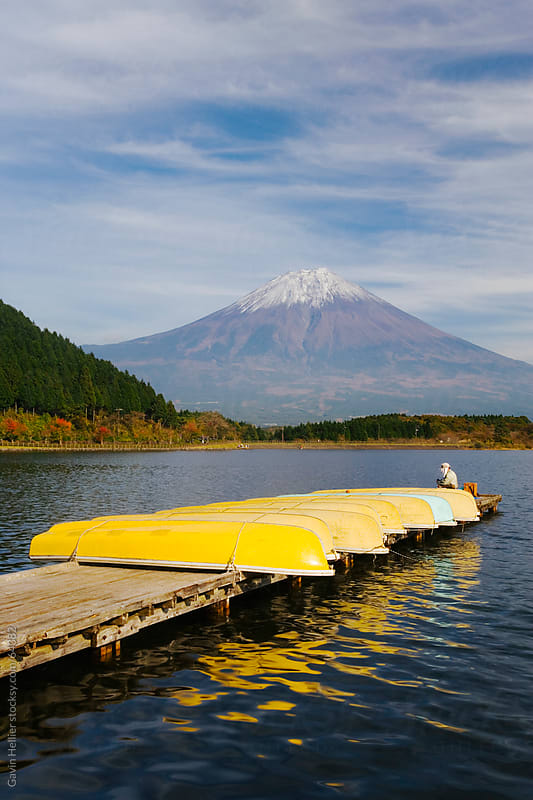 Japan, Honshu, Fuji-Hakone-Izu National Park, men fishing on Lake Tanuki-ko with Mount Fuji in the b by Gavin Hellier for Stocksy United