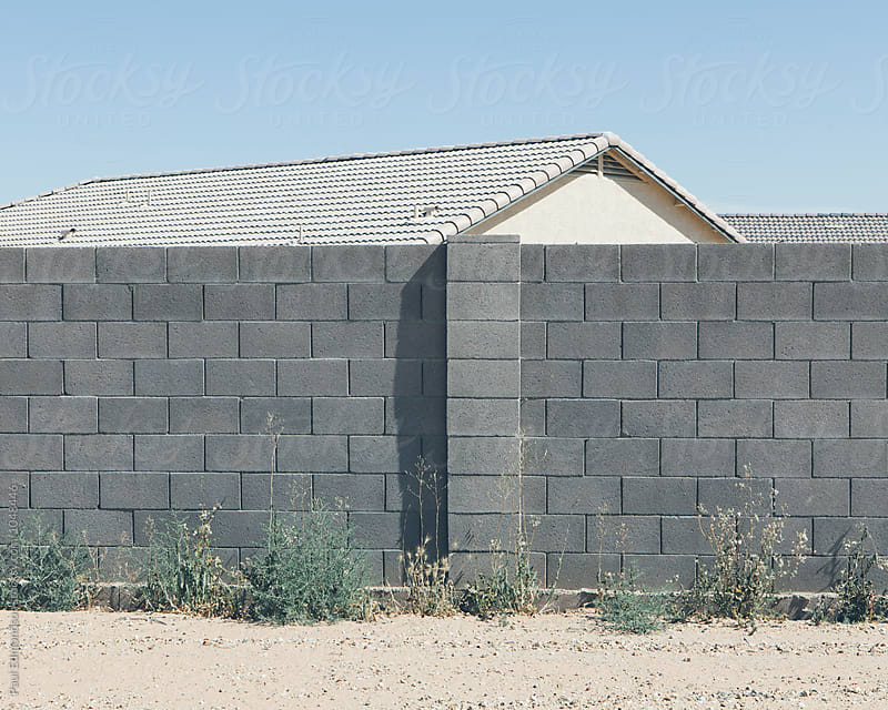 Brick wall in front of suburban housing complex, Pheonix by Paul Edmondson for Stocksy United