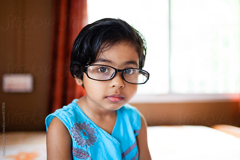Portrait of a cute little girl with glasses in a serious mood by Saptak Ganguly for Stocksy United
