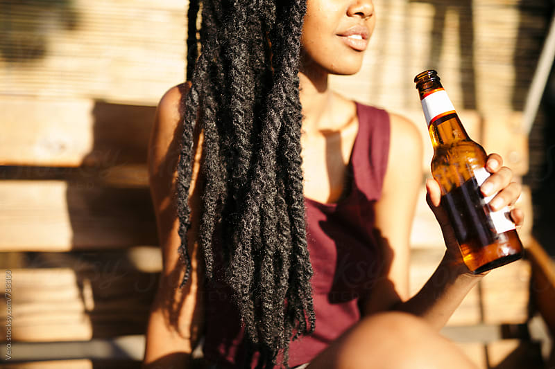 Woman with Dreadlocks having a bottle of beer outdoors by Good Vibrations Images for Stocksy United