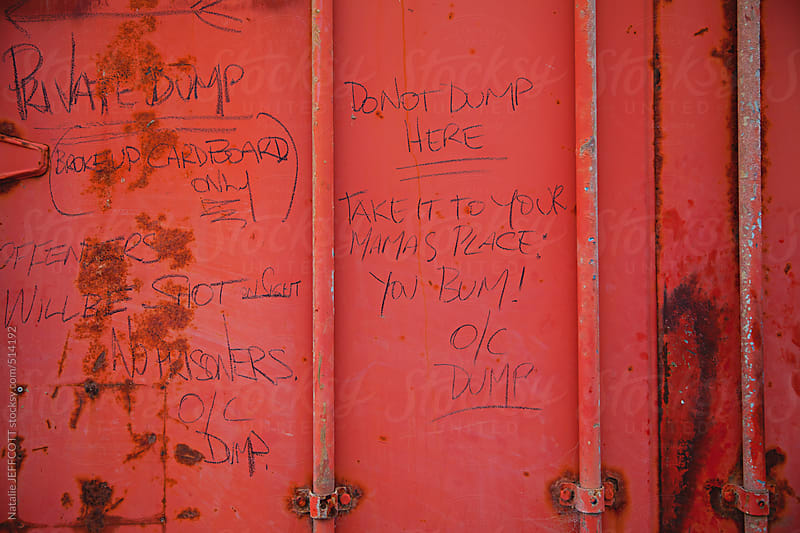 message written on a dump / skip bin outside a restaurant by Natalie JEFFCOTT for Stocksy United