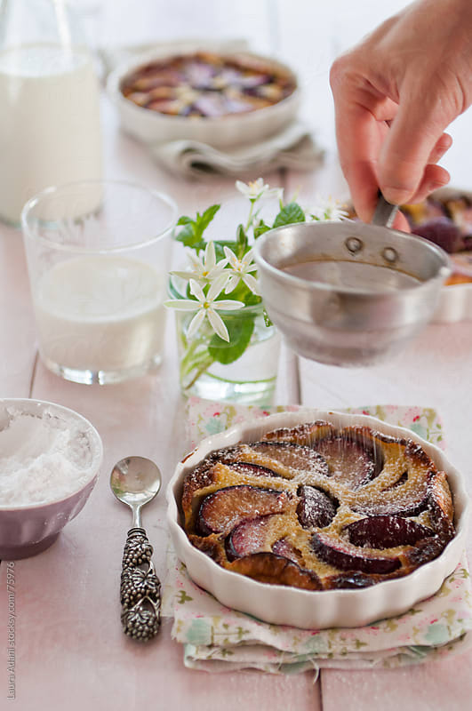 a clafoutis of plum, milk and eggs by Laura Adani for Stocksy United