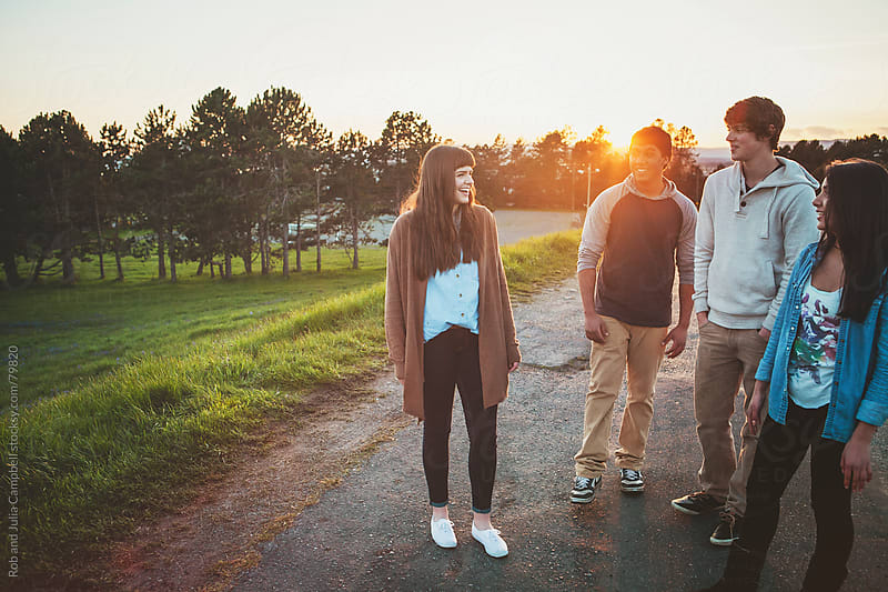 Group of teenagers hanging out having fun at sunset by Rob and Julia Campbell for Stocksy United
