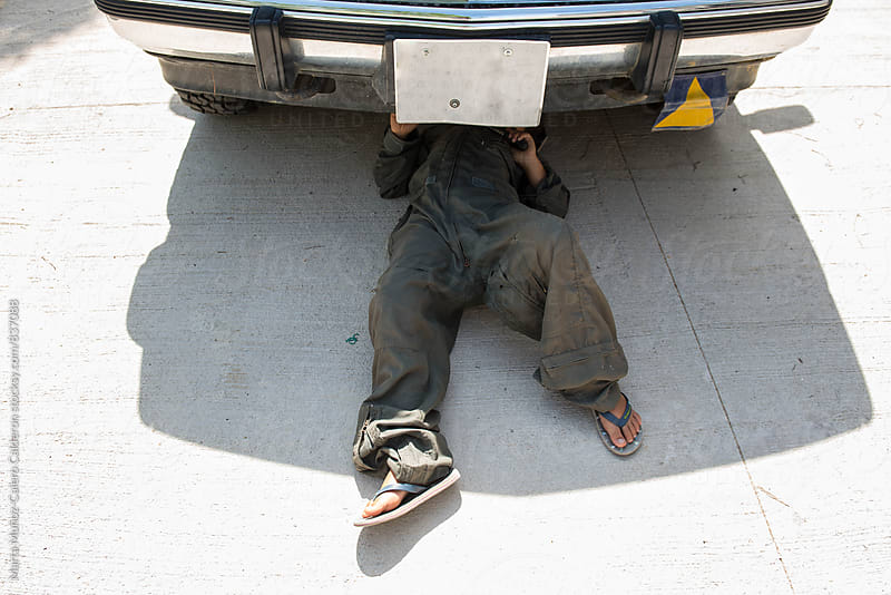 Child under a car fixing an engine by Marta Muñoz-Calero Calderon for Stocksy United
