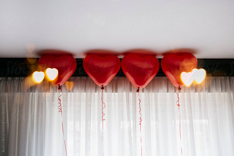 Custom bokeh hearts exposed on 4 red balloons by Beatrix Boros for Stocksy United