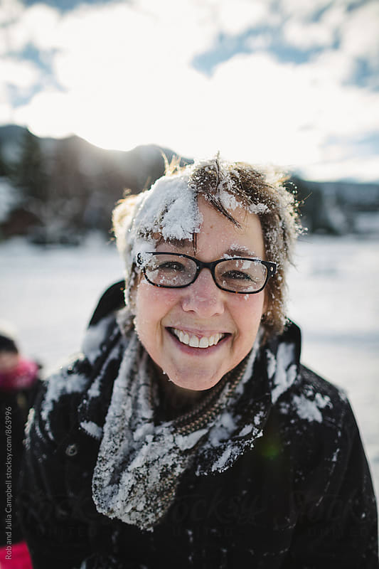 Happy mature woman covered in snow outside in winter (post snow fight) by Rob and Julia Campbell for Stocksy United