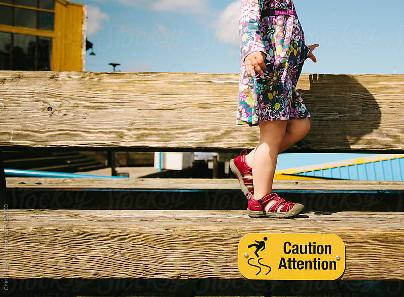 Little girl on a dangerous bench. by Cherish Bryck for Stocksy United