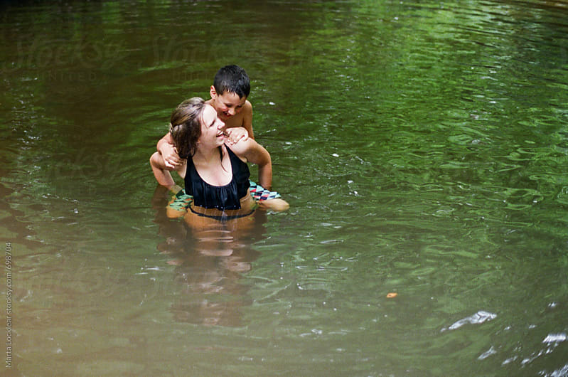 Teen girl playing with her little brother in a river by Marta Locklear for Stocksy United
