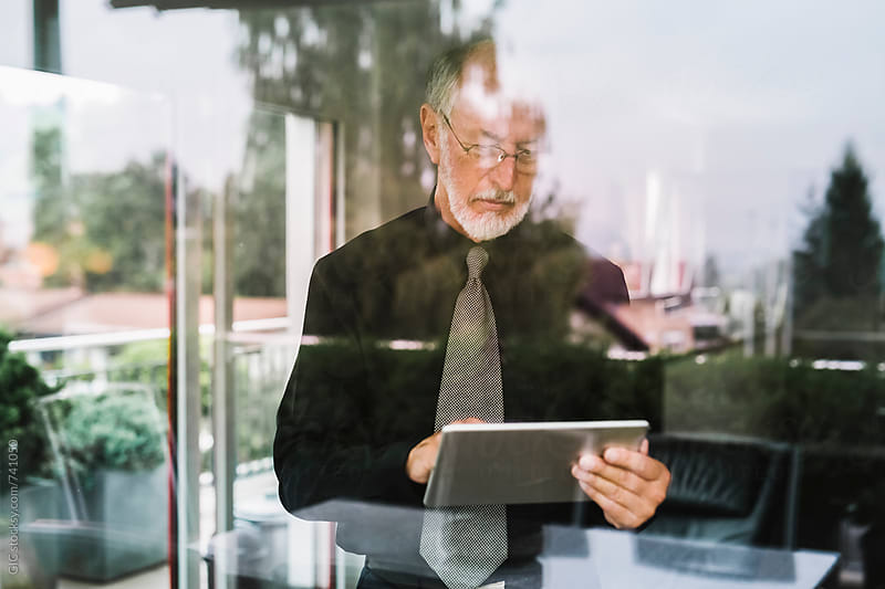 Senior businessman using a digital tablet in the office by GIC for Stocksy United