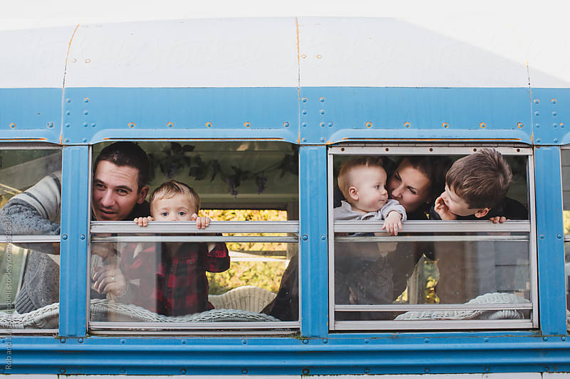 Young family of five looking out bus window by Rob and Julia Campbell for Stocksy United
