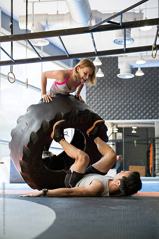 Two workout friends having fun during a tire exercise by Jovo Jovanovic for Stocksy United