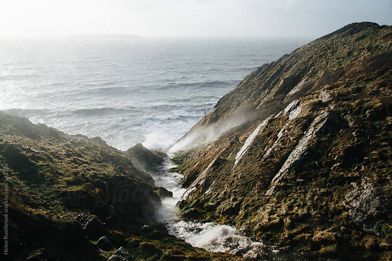 A waterfall being blown back up a cliff on a blustery day by Helen Rushbrook for Stocksy United